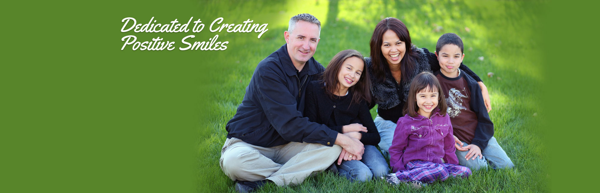 Similing family with young children sitting in the grass - Dedicated to Creating Positive Smiles